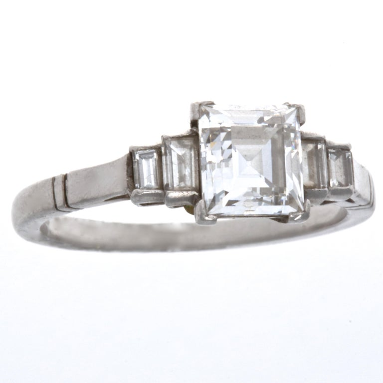 This ring is a reminder of the enduring creativity of the Art Deco era. The Art Deco style carre cut diamond is GIA certified as 1.17 carats, E color VVS2 clarity. Accented with four emerald cut diamonds weighing approximately 0.35 carats G,H color