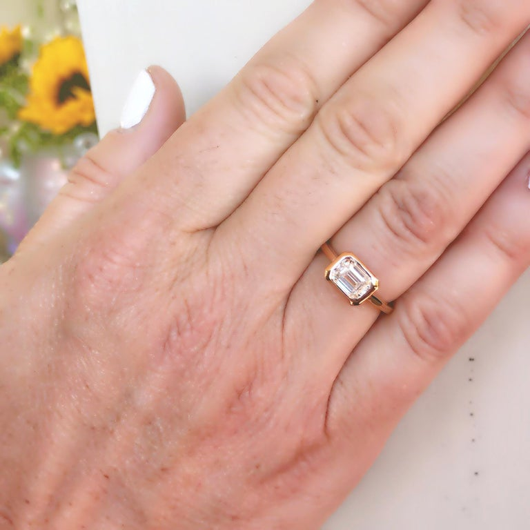 Classic yet with a modern twist, this 18k rose gold solitaire ring appeals to contemporary tastes! Featuring a GIA emerald-cut diamond, I color and VS1 clarity, with beautiful flash, excellent to very good attributes, and bezel-set in horizontal