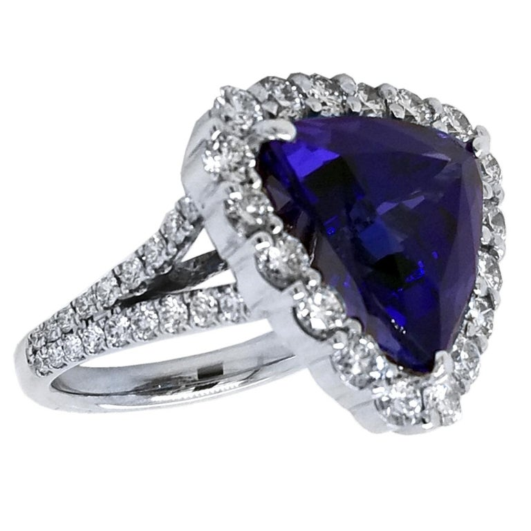 A beautiful color 12.40 Ct Trillion shaped tanzanite set in the center of an 18K split shank pave set diamond engagement ring with a halo to create great contrast.   Details: Center Stone: 12.40 carat Trillion tanzanite Side Stone Diamonds: 2.30