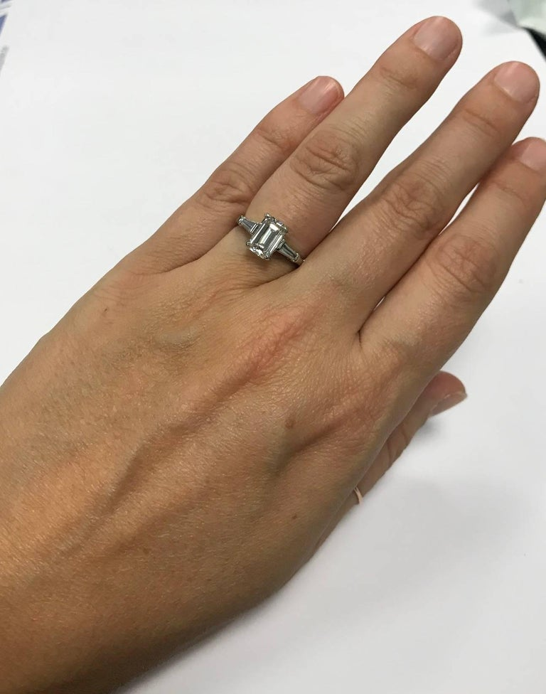 Beautiful emerald cut diamond mounted in a platinum ring with two tapered baguettes on the sides weighing approximately .25 carat The center diamond has a certificate from the Gemological Institute of America stating that it is