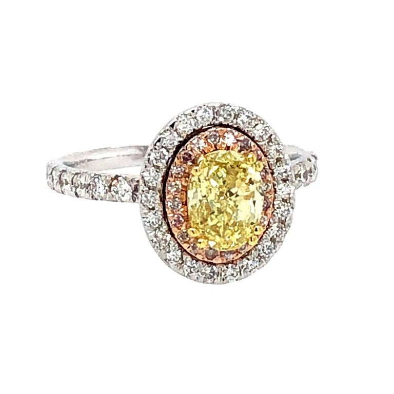 Offered here is a beautiful Gia certified natural fancy intense yellow oval shape diamond with pink and white diamonds set in 18kt gold ring.  Center diamond has a GIA report# 17177771 Oval 1.02 carat diamond fancy intense yellow, VVs1 clarity.