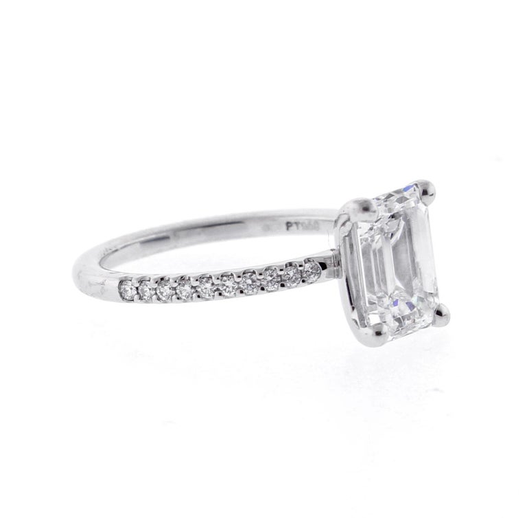 A perfectly proportioned Emerald Cut Diamond Solitaire sits on a band on diamonds ♦ Metal: Platinum ♦ Diamond=2.02 carats I color VS1 clarity ♦  20 Diamonds=.15 ♦ Circa 2018 ♦ Size 6, Resizable ♦ Packaging: Pampillonia presentation box  ♦ Condition: