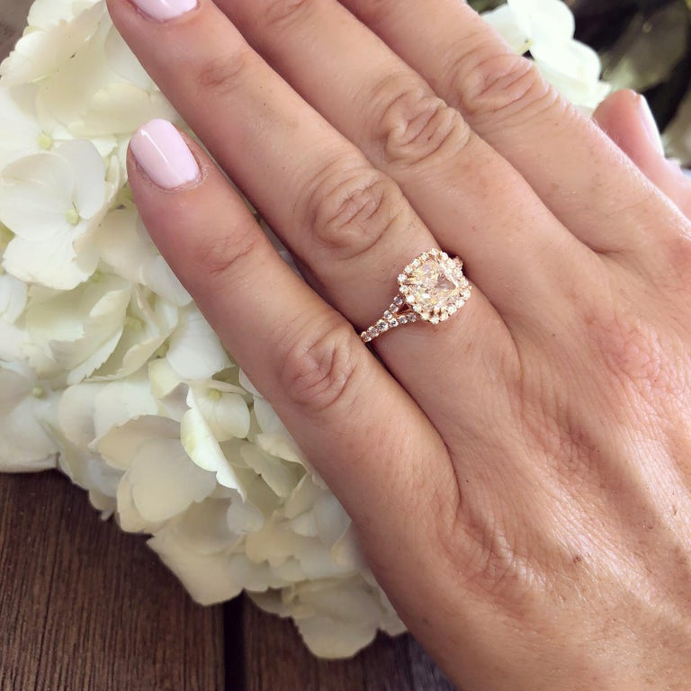 Set in 18k rose gold, the gorgeous engagement ring features a GIA 2.00 carats cushion-cut diamond, I/VVS1, with a surrounding halo and shoulders set with 48 round brilliant-cut diamonds weighing in total approximately 0.68ct. The ring weighs 4.6