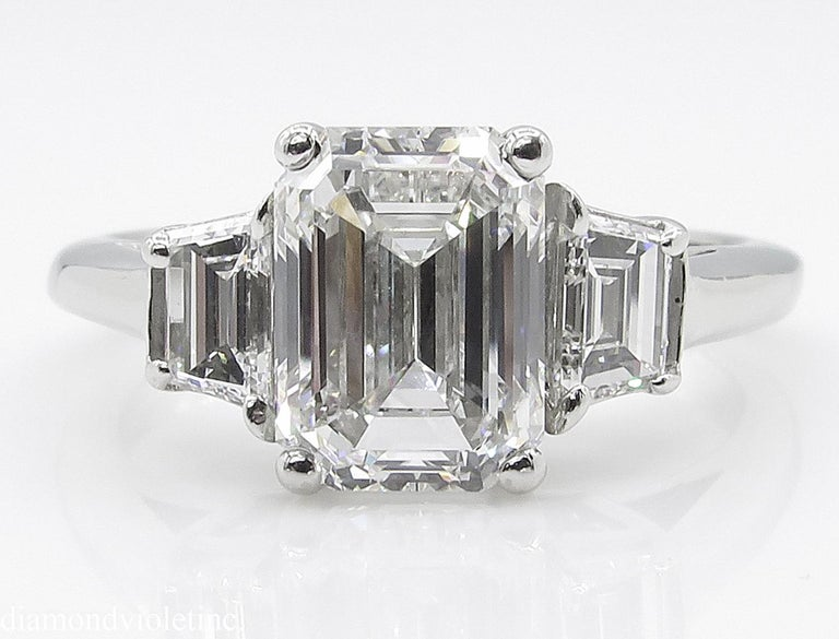 A Breathtaking Vintage HANDMADE PLATINUM (stamped) Emerald Diamond Three-Stone Engagement ring. The Prong Set Emerald Diamond is estimated 2.02CT with measurements of 8.24X6.10X4.19mm. GIA Certified in F color SI1 clarity (COLORLESS and Eye
