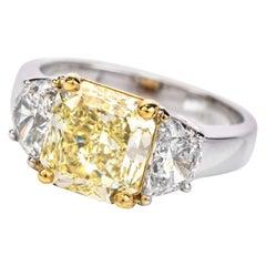 GIA 2.94 Carat Fancy Light Yellow Diamond 18 Karat Gold Radiant Three-Stone Ring