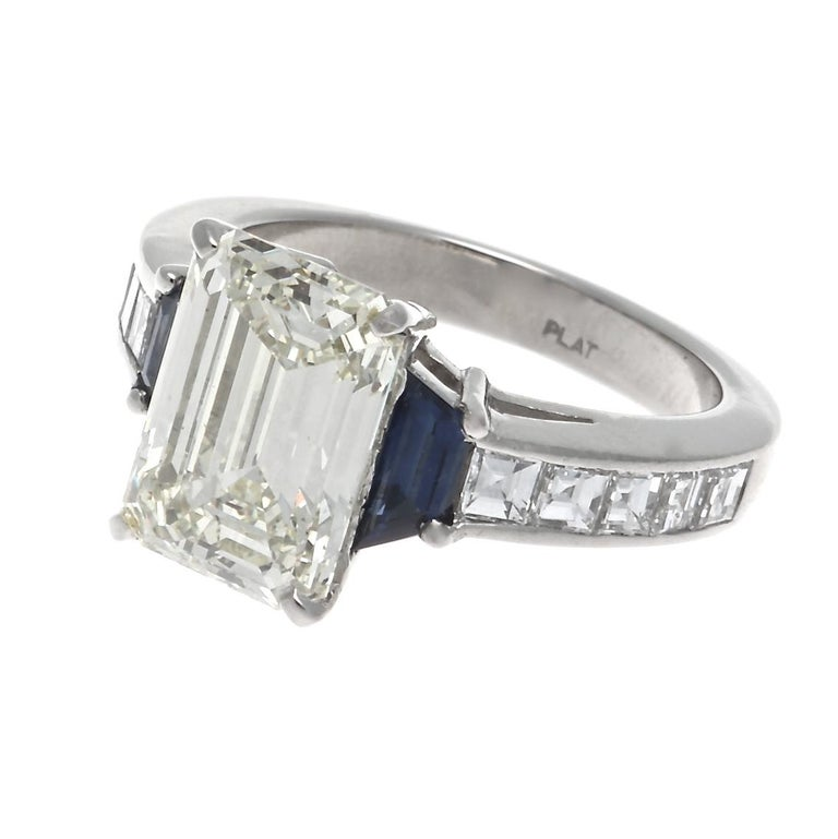 It's all champagne and sunshine with this GIA 3.44 carat O-P color, VS2 prong set emerald cut diamond ring. Framed by two perfectly suited faceted trapezoid cut sapphires and channel set square emerald cuts on the platinum band. Size 5 1/2, sizing