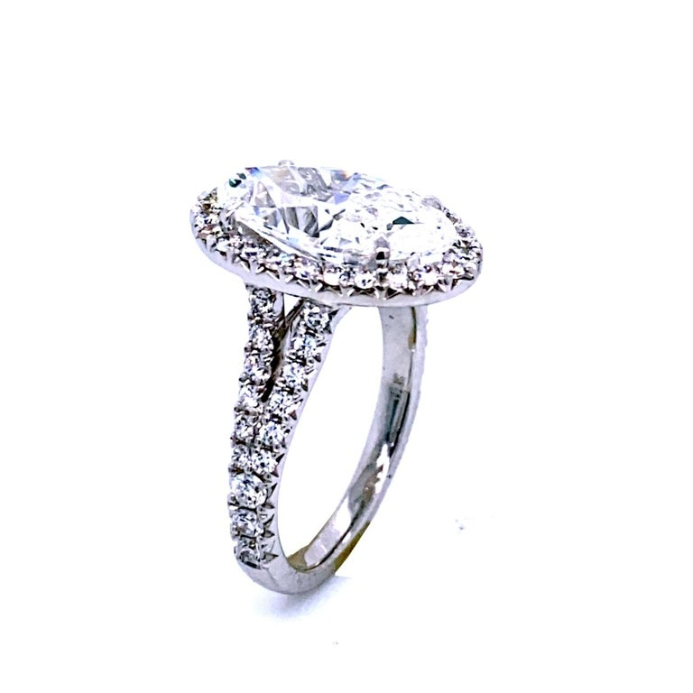 A very fine Oval F/VVS2 GIA certified Diamond set in a fine 18k gold French-Pave set Engagement Ring with halo. Total diamond weight of 0.87 Ct. on the side.   Diamond specs: Center stone: 4.10 Ct GIA Certified F/VVS2 Oval natural diamond Center