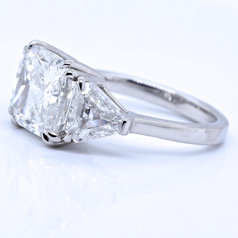 If you are a strong, independent woman, or are looking to marry one, this Jack Weir and Sons GIA 4.54 carat Three Stone Diamond Platinum Engagement Ring is what you need! Full of character and charisma, the center diamond is a GIA certified cushion