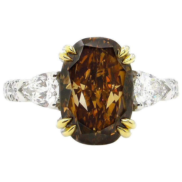 GIA 4.85 Carat Natural Fancy Brown Orange Oval Cut Diamond 3-Stone Platinum Ring For Sale