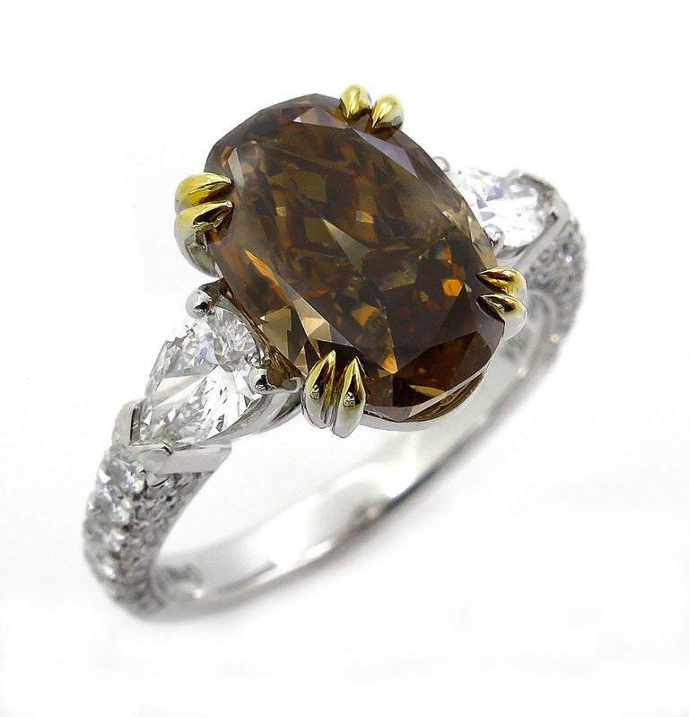 GIA 4.85 Carat Natural Fancy Brown Orange Oval Cut Diamond 3-Stone Platinum Ring In Good Condition For Sale In New York, NY