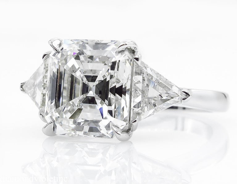 A Breathtaking Estate HANDMADE PLATINUM (stamped) Asscher cut Diamond Three-Stone Engagement ring. The Prong Set Asscher Diamond is 4.22CT with measurements of 9.74x9.20x5.79mm; GIA Certified as J color and VS2 clarity (Eye Clear). GIA report #