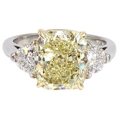 GIA 5.55 Carat Fancy Light Yellow Cushion Diamond Three-Stone Platinum Ring