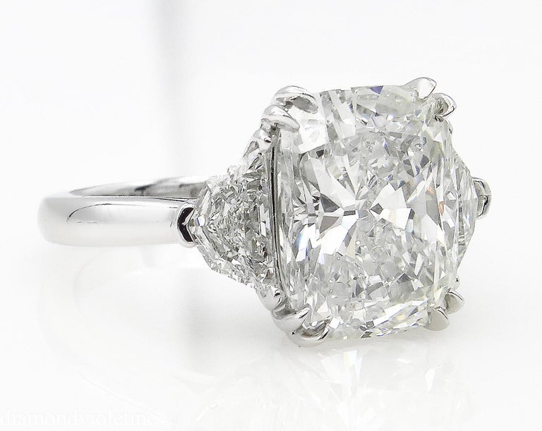 A Breathtaking Estate HANDMADE PLATINUM (stamped) Cushion Diamond Three-Stone Engagement ring. The Prong Set Radiant Diamond is 5.02CT with measurements of 11.58x9.20x6.08mm. GIA Certified as K color and I1 clarity (Eye Clean). It is set with 2