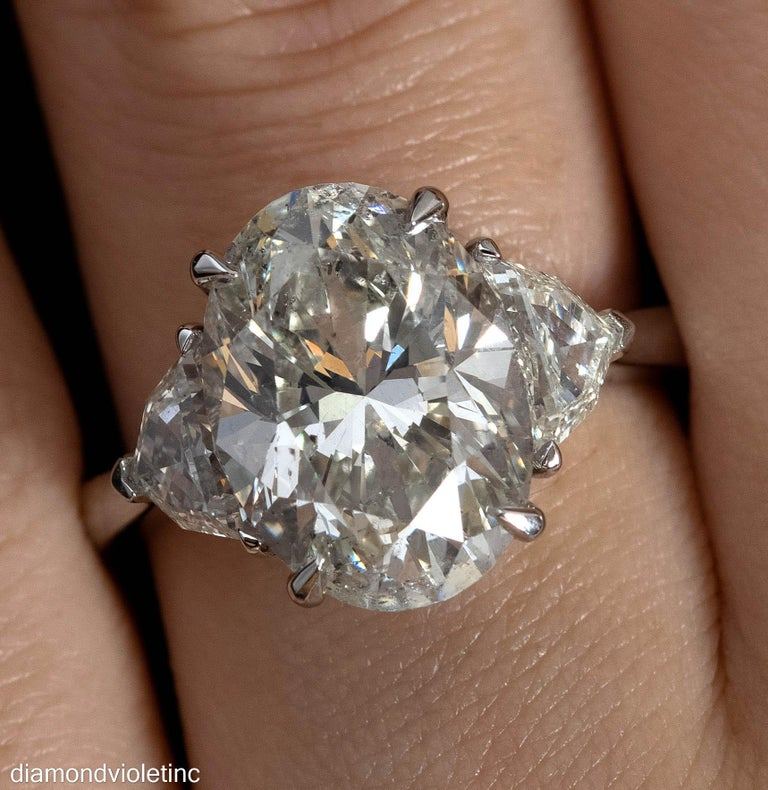 A Breathtaking Estate HANDMADE PLATINUM (stamped) Oval Diamond Three-Stone Engagement ring. The Prong Set Oval Shaped Center Diamond is GIA Certified 5.31CT; with measurements of 13.02x9.35x6.47mm in M color I1 clarity (slight yellow tint; eye
