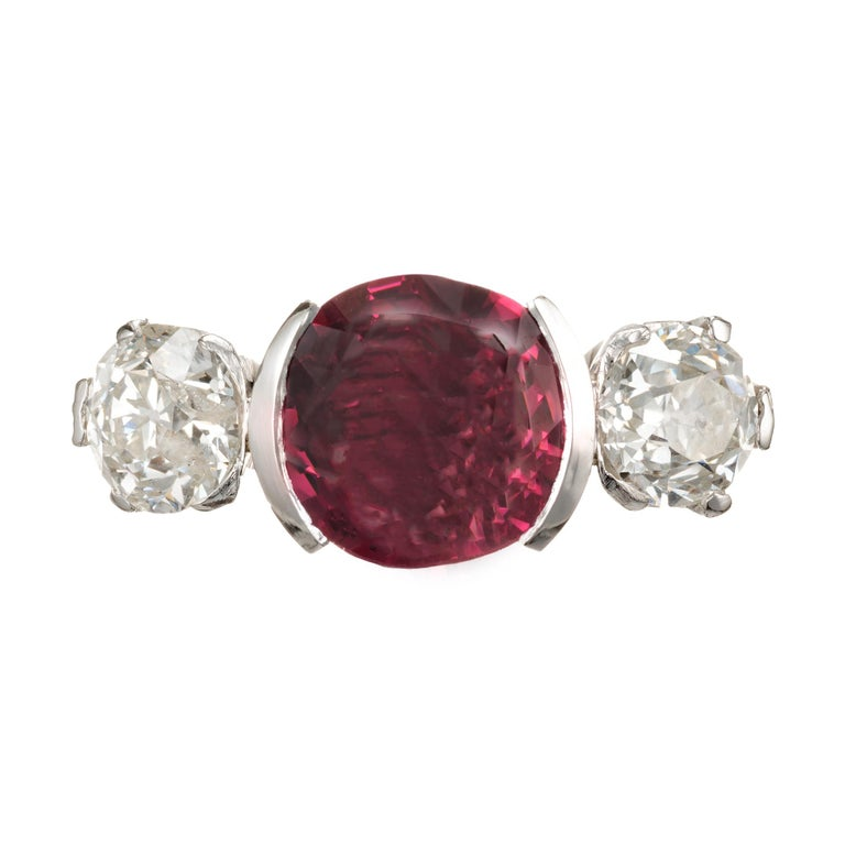 1920's Spinel and diamond three-stone engagement ring. Cushion cut pink Spinel half bezel set center stone with two old mine brilliant cut side diamonds. GIA certified no heat Spinel of 3.75cts of old cut.  1 cushion purplish pink Spinel, approx.