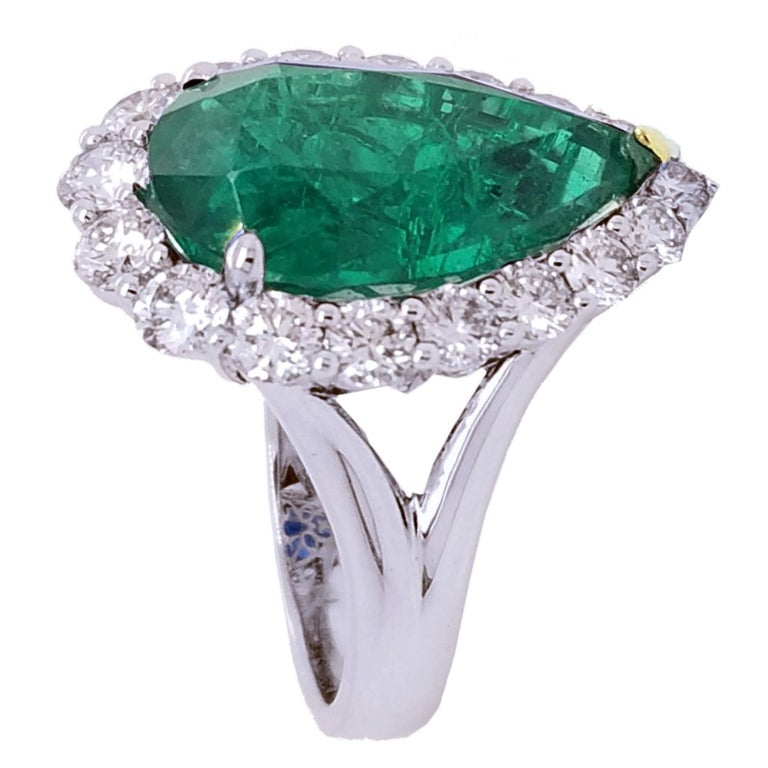A beautiful color GIA Certified 8.90 Ct Pear shaped Emerald  set in the center of an 18K split shank diamond engagement ring with a halo to create great contrast.   Details: Center Stone: GIA certified 8.90 carat Pear shaped Emerald Side Stone