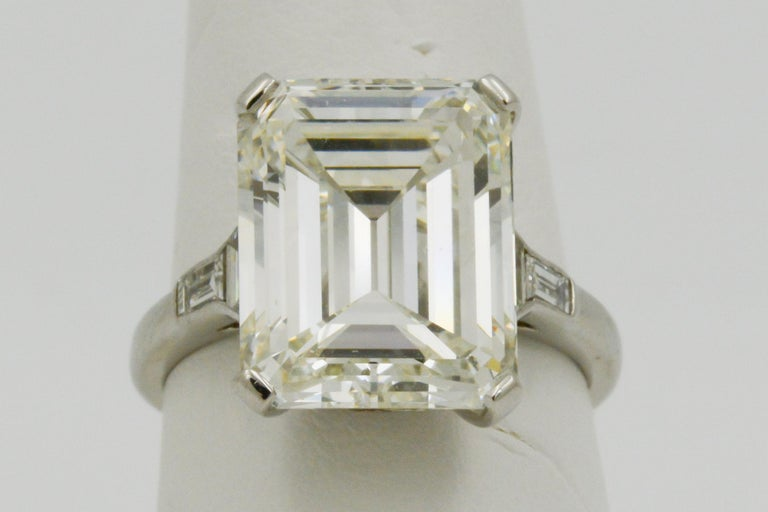 This platinum five stone ring features a 9.66 Emerald cut diamond that has K color and S1 clarity. The ring is GIA certified. It also showcases two trapezoid and two tapered baguette diamonds that weigh a total of .32 carats with I-J coloring and VS