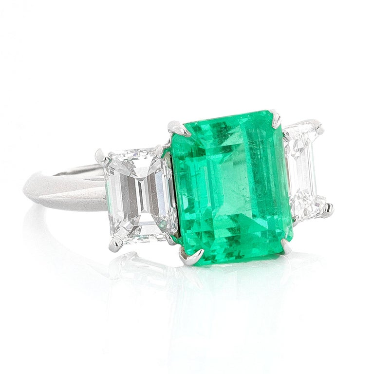 Platinum three stone emerald ring with diamond side stones. The center stone is AGL certified and the side stones are GIA certified. AGL describes the center stone as a 4.27 carat, emerald cut emerald. The emerald is natural, green, and has Minor