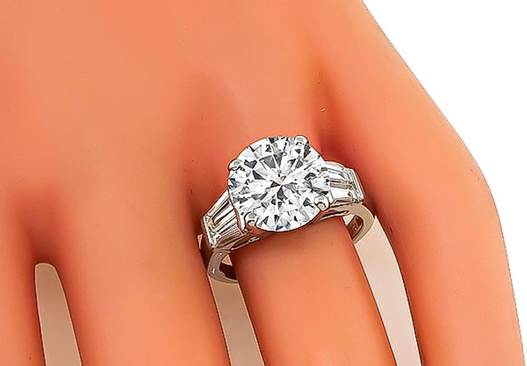 This amazing platinum engagement ring is set with sparkling GIA certified round brilliant cut diamond that weighs 4.00ct. graded E color with I1 clarity. Accentuating the center stone are dazzling baguette cut diamond accents. The ring is stamped