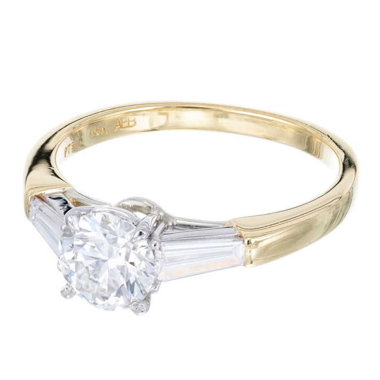 Diamond engagement ring. Platinum and 18k yellow gold three-stone setting with a GIA certified round center diamond and two tapered baguette side diamonds.   Ideal cut diamond, approx. total weight .90cts, and 6.18 x 6.24 x 3.85 mm, F, VVS1, Depth: