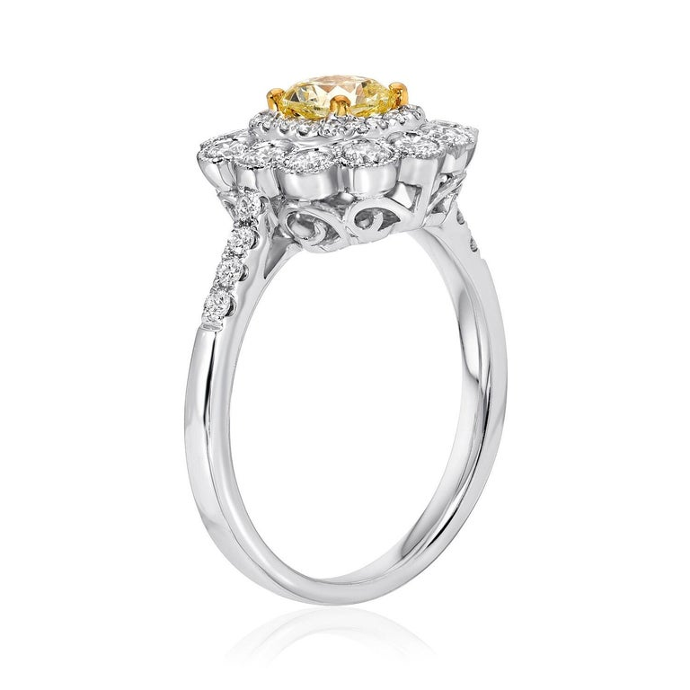 GIA certified 0.58 carat Fancy Light Yellow to Fancy Yellow cushion cut diamond, surrounded by 12 round brilliant diamonds weighing a total of 0.48 carats, and a total of 0.21 carats of round brilliant diamond melee, all hand set in an 18K white,