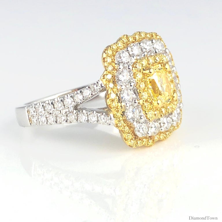 This gorgeous ring features a 0.68 carat GIA Certified Natural Fancy Yellow Cushion Modified Brilliant center, surrounded by halos of round yellow and round white diamonds. Additional round diamonds trailing down the split shank bring the total
