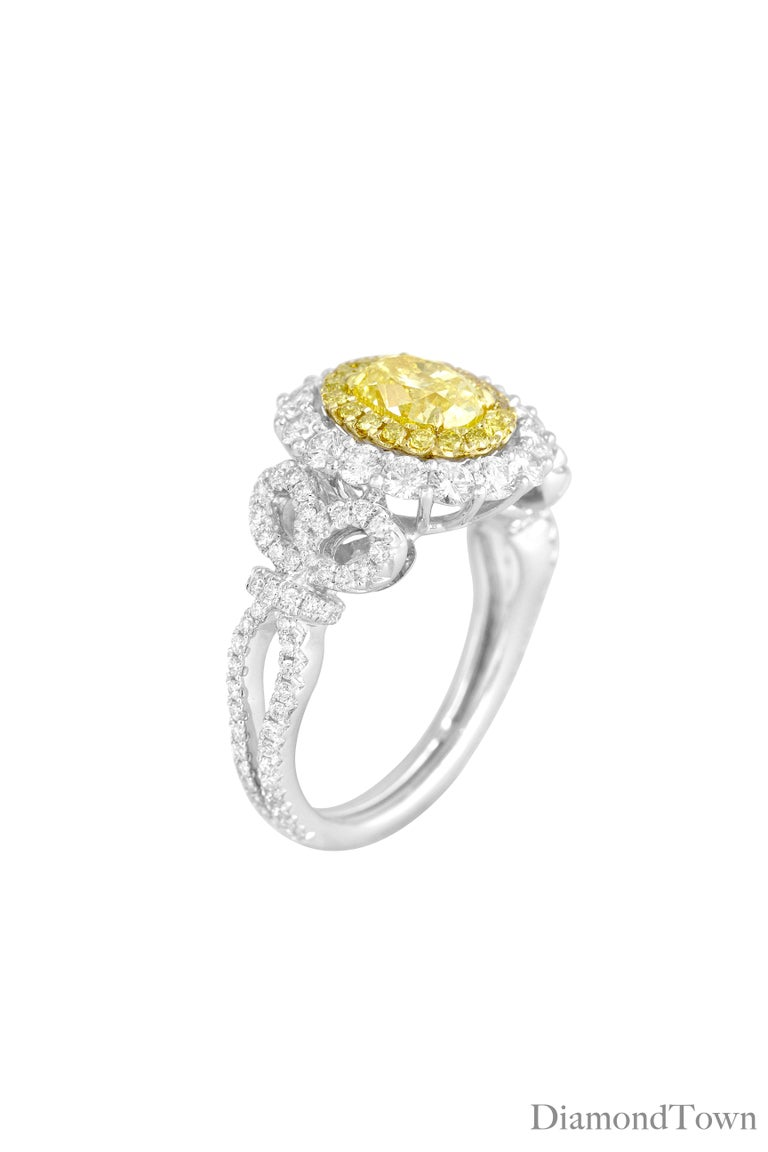 This gorgeous ring has a GIA Certified Oval Cut Natural Fancy Intense Yellow center measuring 0.98 carats, surrounded by a halo of round white diamonds. Additional diamonds decorate the side shank, including in a delicate bow design along the side