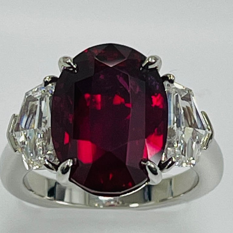 10.07 Carat Oval shape Mozambique ruby certified by GIA lab set in hand made platinum three stone ring along with 1.26 carat epulette collection quality fancy cut diamonds .