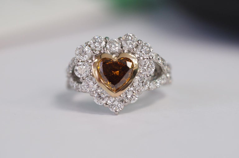 This Center is a Natural, fancy deep brownish yellowish orange Heart diamond with GIA certificate, no.1308992514. It weighs 1.01 carats and is  SI2  in clarity. The dimensions are 6.54 x 7.05 x 3.04mm. It is bezel set with 18k yellow gold. This ring