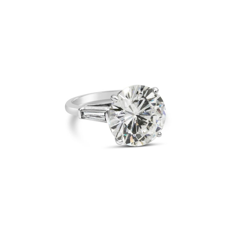 A classic engagement ring showcasing a 10.11 carat round diamond certified by GIA as K color, SI1 clarity, set in a thin four-prong platinum mounting. Accented by two baguette diamonds weighing 1.02 carats total. Size 7 US (sizable upon