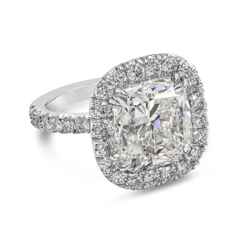 A chic jewelry piece showcasing a 10.12 carat cushion brilliant diamond certified by GIA as J color, SI1 clarity. Surrounding the center diamond is a row of round brilliant diamonds, set in an accented basket and band made in platinum. Accent