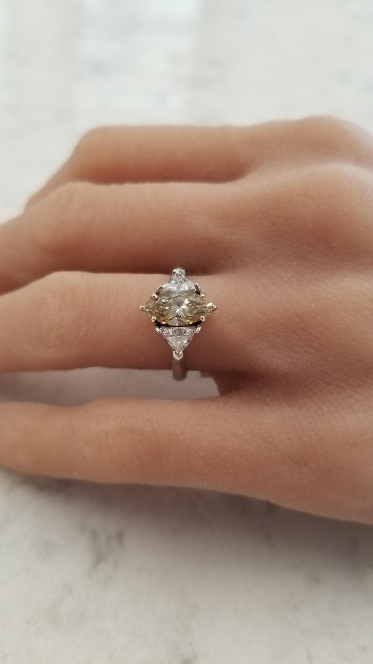 This ring features a GIA certified 1.08 carat marquise cut that is natural fancy brownish-yellow diamond, prong set, with measurements of 11.86 X 5.37 and SI1 clarity. It's accentuated by rich 18 K yellow gold. The stunning color of this diamond is