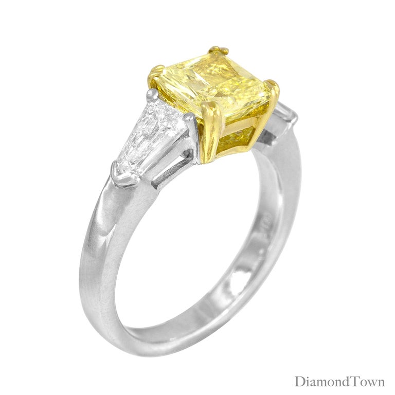 This gorgeous ring features a GIA Certified Square Modified Brilliant 1.08 Carat Fancy Light Yellow Diamond center, flanked by two tapered baguette white diamonds. The total diamond weight is 1.60 carats.  Set in Platinum and 18k White Gold. This
