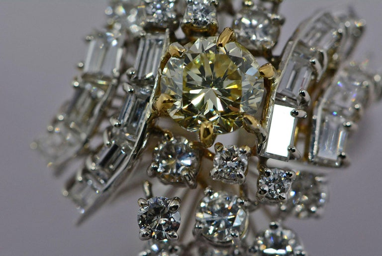 This ring will make a statement as soon as you walk into the room.  The center diamond has a wonderful light yellow colour and although it has been graded an I1 by GIA, we refer to it a