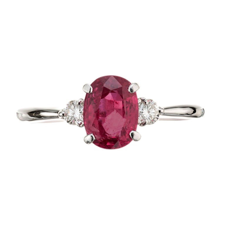 Ruby and diamond three-stone engagement ring. GIA certified oval natural corundum- ruby heated with moderate residue in a platinum setting with 2 round brilliant cut side diamonds.  1 oval red ruby, SI approx. 1.11cts GIA certificate # 6214312056 2