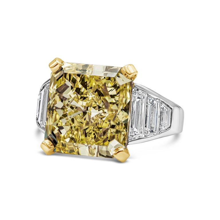 Features a color-rich radiant cut diamond weighing 11.30 carats, flanked by custom-cut trapezoid diamonds channel set in platinum. Accent diamonds weigh 2.08 carats total. Accompanied with a GIA report certifying the center diamond as Fancy Intense