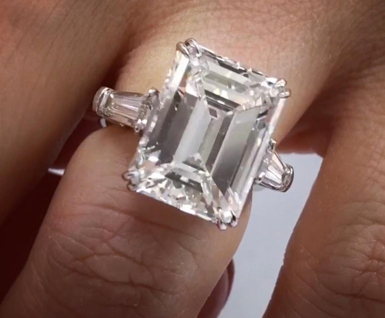 Platinum Three stone Emerald cut Diamond Ring. The center stone is 11.34 Carats H Color VS1 in Clarity Emerald Cut, set with 1.38 Carats of Baguettes on each side. In Platinum