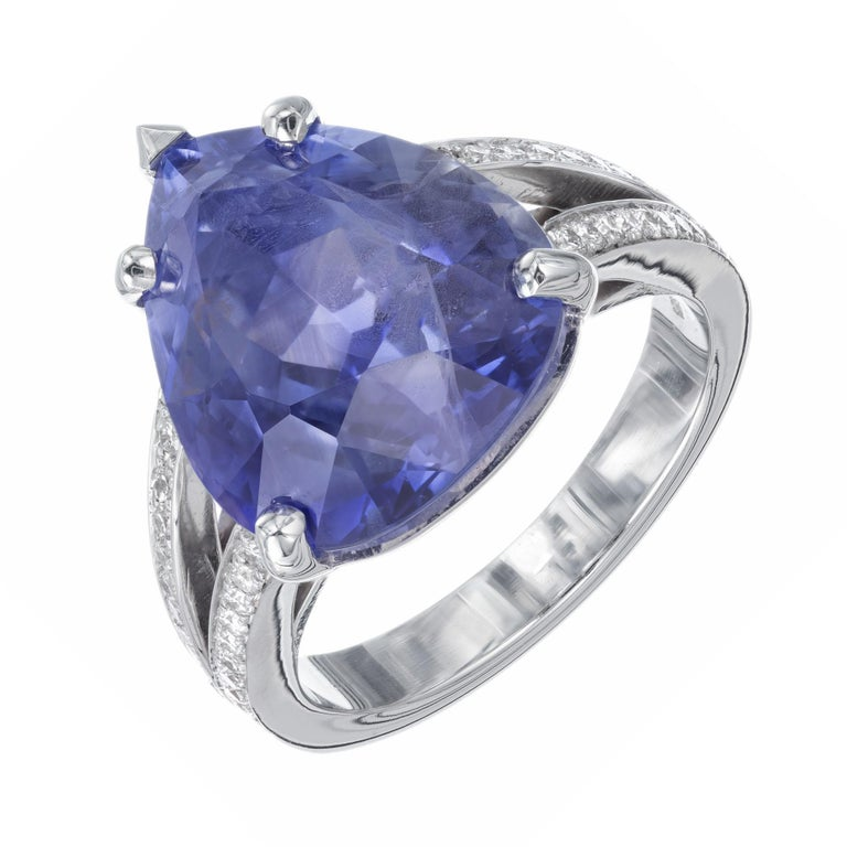 Sapphire and diamond engagement ring. Pear shaped sapphire center stone set in a platinum setting with 48 round ideal cut diamonds.  There are natural veil type flaws and feathers that partially separate the color zones.   1 pear shaped blue