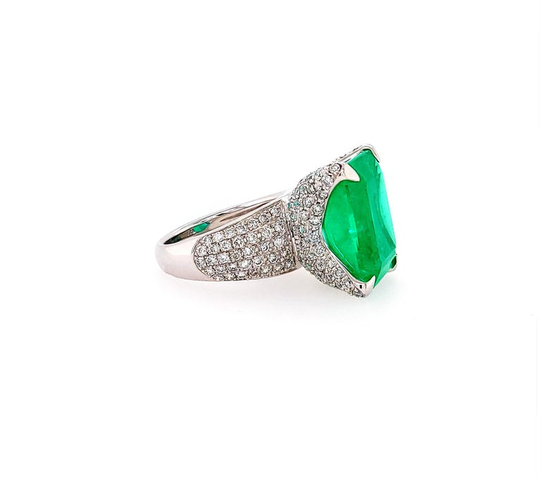 A stunning cocktail ring featuring a 13.35 carat octagonal step-cut emerald surrounded by white diamonds.  The emerald is accompanied by a GIA report, stating that the stone is of Colombian origin with minor clarity enhancement.  Total weight of the