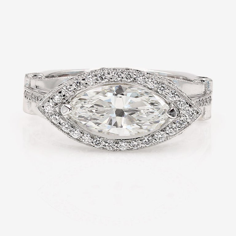This Lester Lampert original setting in 18kt. white gold features a 1.42cts. marquise cut center that is H in color and VVS1 in clarity. The center is set sideways and is surrounded by 138 ideal cut round diamonds=.85ct. t.w. The round diamonds are