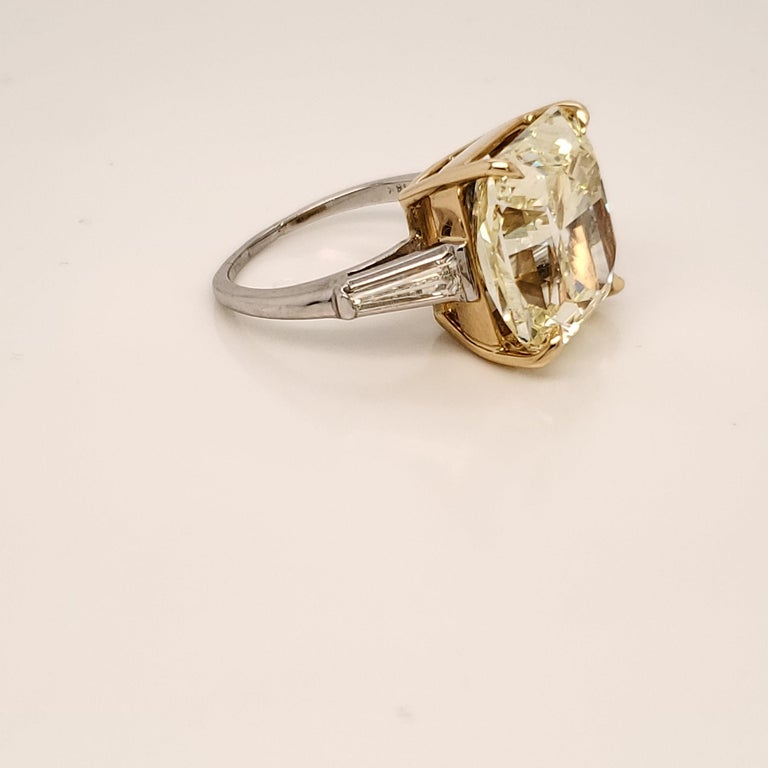 GIA certified three stone ring. The center stone is 15.06 carats fancy Yellow SI1. The side diamonds are tapered baguettes weighing approximately 0.40 carats. The diamonds are set in platinum and 18k yellow gold.