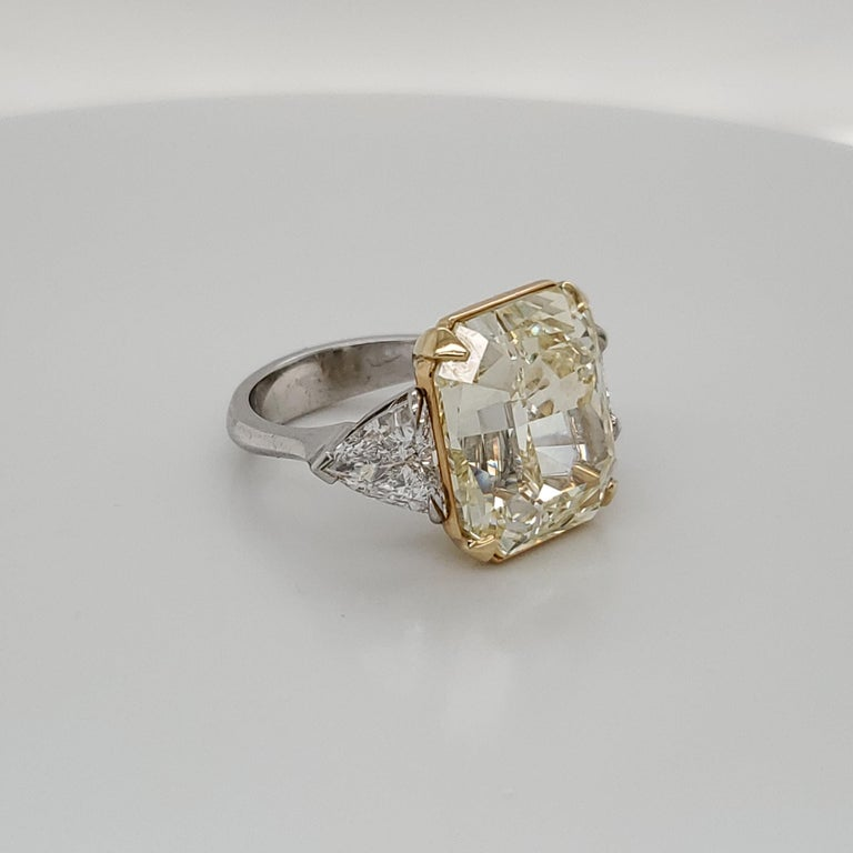 GIA Certified 15.07 Fancy Yellow VS1 center diamond set in Platinum and 18k yellow gold with 2 trillion shaped diamonds weighing about 1.98 carats total