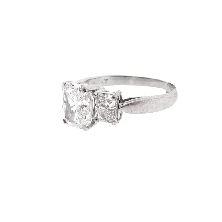 This is a GORGEOUS GIA Certified, 1.53 carat E-Si1 radiant diamond, three-stone engagement ring with side stones. This diamond is super white and of extremely high quality. This is the second whitest color diamond available. The stone is set between