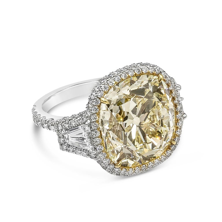 An important piece of jewelry showcasing a 15.52 carat cushion cut yellow diamond, certified by GIA as Fancy Yellow color, VS1 clarity. The center diamond is flanked by tapered baguette diamonds and is surrounded by round brilliant diamonds. Accent