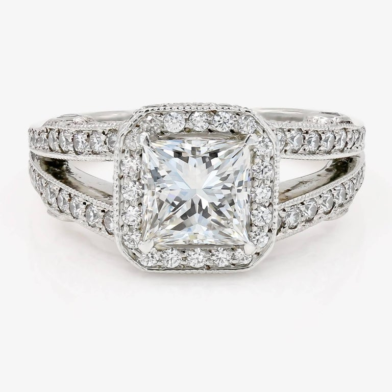 This classic platinum ring contains a 1.57cts. princess cut center G color and SI1 clarity, with 154 ideal cut round diamonds= 1.01cts. t.w. set in a halo style around the center and down the sides of the split shank. (accent diamonds are