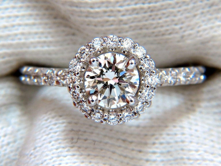 GIA Certified Diamond engagement ring.   Halo Classic  GIA Certificate:  2185151531  .71ct.  Natural Round Cut diamond  K color VVs2 clarity   (Please see report copy attached)  .90ct Side Natural round diamonds:  G-color, Vs-2 clarity.  14kt. white