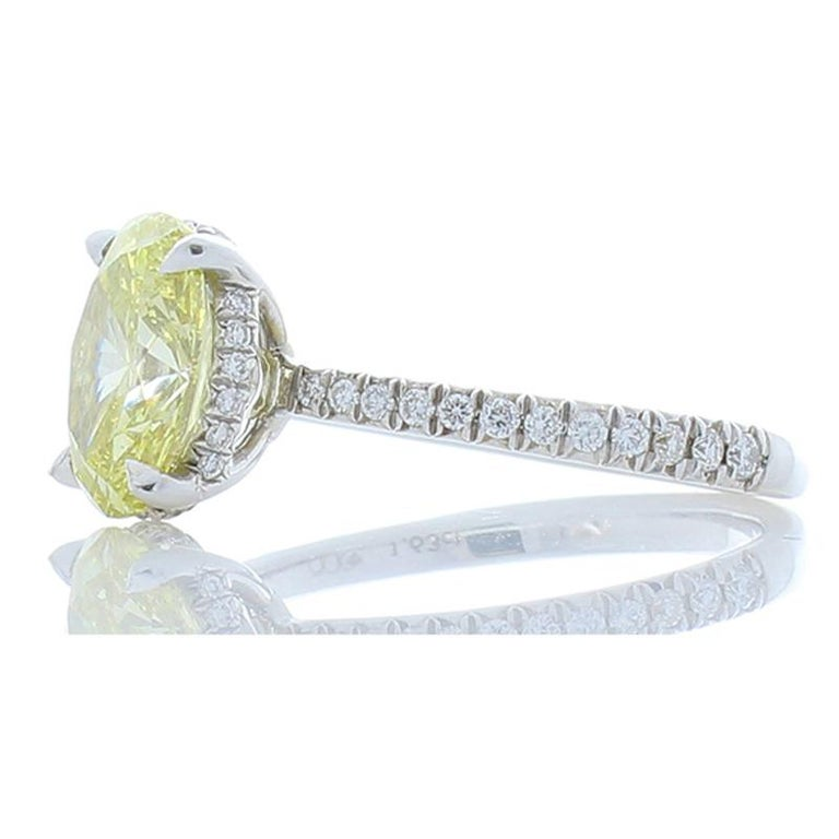 This stunning ring will delight her for a lifetime! The eye fixates first, on the exceptionally striking lemon fancy yellow that is GIA certified weighing 1.63 Carat- 8.89 X 6.80 millimeter oval diamond. Then, your eye is drawn to the 0.25 carat