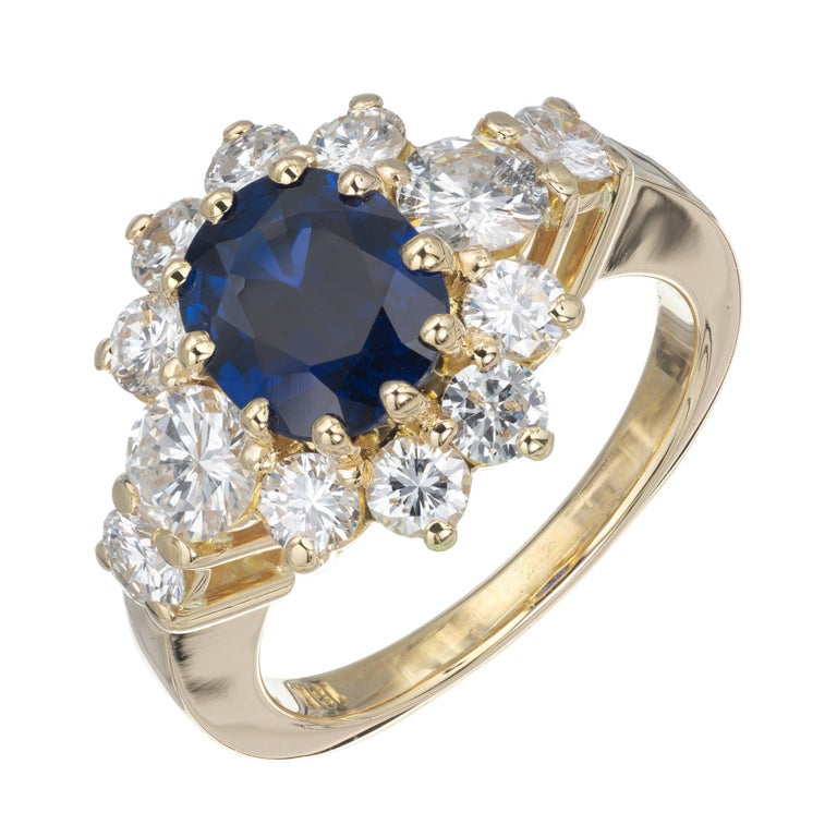 Royal blue 1.69 carat oval sapphire and diamond engagement ring. GIA Certified natural no heat no enhancements center stone, with a halo of round brilliant cut diamonds. 18k yellow gold setting.   1 oval dark blue sapphire VS, approx. 1.69cts GIA