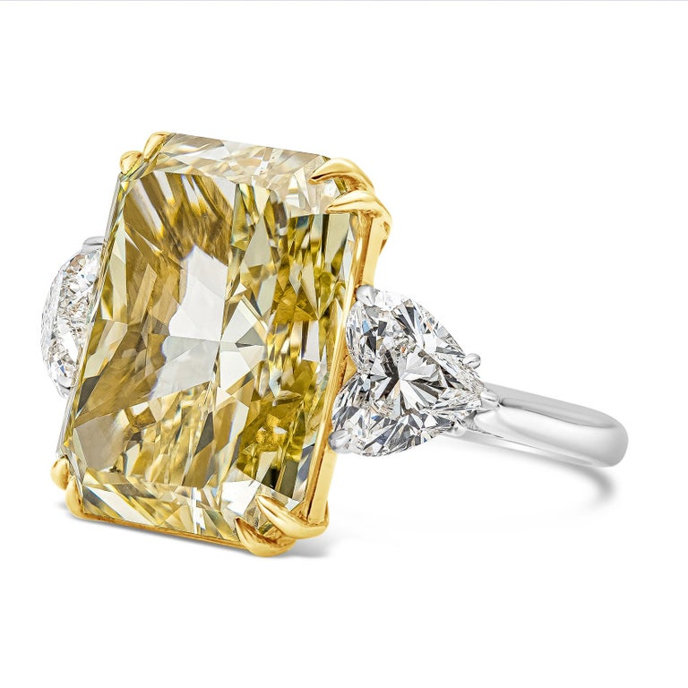 A unique and well-crafted three-stone ring style featuring a vibrant 17.25 carat elongated radiant cut diamond certified by GIA as Fancy Intense Yellow color, VS2 clarity. Flanking the center diamond are brilliant heart shape diamonds weighing 2.08