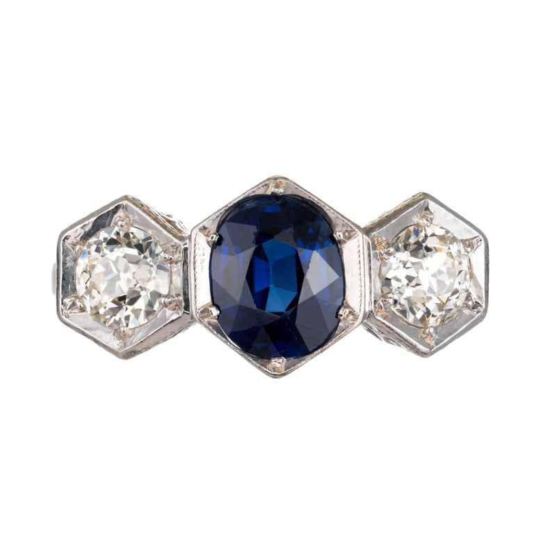 Art Deco Oval sapphire and old euro diamond engagement ring. Three-stone setting in platinum with a center sapphire and two side diamonds. open flower scroll work.    1 Oval blue sapphire no heat 7.14 x 5.65 x 3.65 approximate 1.15 carat GIA